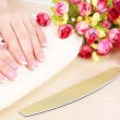 Beautiful woman hands with french manicure and flowers on wooden background — Stock Photo