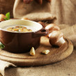 Composition with mushroom soup in pot, fresh and dried mushrooms, on wooden table, on sackcloth background — Stock Photo #41856399