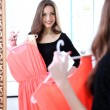 Stock Photo: Young beautiful womtrying dress front of mirror in room
