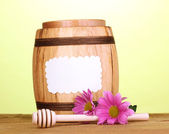 Sweet honey in barrel with drizzler on wooden table on green background — Stock Photo