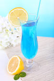 Glass of cocktail on table on light blue background — Stock Photo