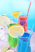 Glasses of cocktails on table on light blue background — Stockfoto
