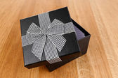 Open gift box on wooden background — Stock Photo