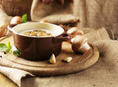 Composition with mushroom soup in pot, fresh and dried mushrooms, on wooden table, on sackcloth background — Stock Photo