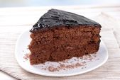 Delicious chocolate cake on plate on table close-up — Stock Photo