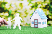 Little house and paper people on green grass, on bright background — Stock Photo