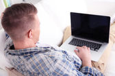 Handsome young man sitting on couch with laptop in room — Stock Photo