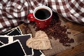 Composition with coffee cup, decorative hearts, plaid spices and old blank photos, on wooden background — Stock Photo