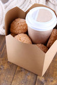 Hot coffee and cookies in box on wooden table close-up — Stock Photo