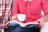 Kanepenin üstüne oturan kadın okuma kitabı ve içecek kahve veya çay, yakın çekim — Stok fotoğraf