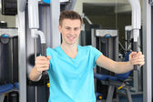 Young man training with weights in gym  — Stock Photo
