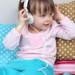 Little girl sitting on pillows on wall background — Stock Photo