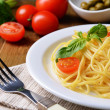 Delicious spaghetti with tomatoes on plate on table close-up — Stock Photo #41891251