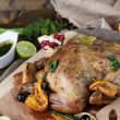 Whole roasted chicken with vegetables and fried potatoes on wooden board, on wooden background — Stock Photo