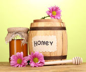 Sweet honey in barrel and jar with drizzler on wooden table on green background — Stockfoto