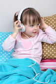 Little girl sitting on pillows on wall background — Stockfoto
