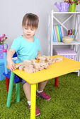 Little girl plays with construction blocks sitting at table in room — Stock Photo