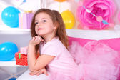 Pretty little girl sitting on sofa on celebratory background — Stock Photo