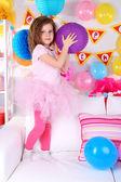 Pretty little girl on sofa on celebratory background — Stock Photo
