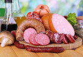 Different sausages on wooden table on natural background — Stock Photo