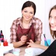 Stock Photo: Beautiful girl manicurist doing manicure for womin beauty salon