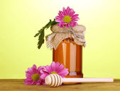 Sweet honey in jar with drizzler on wooden table on green background — Stock Photo
