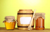 Sweet honey in jars and barrel with drizzler on wooden table on green background — Stock Photo