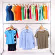 Different clothes on hangers, on gray background — Stock Photo #42010021