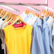 Different clothes on hangers, on pink background — Stock Photo #42010025