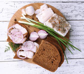 Slices of bread and lard with onion on cutting board on wooden background — Stock Photo