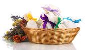 Textilní sáček váčky s sušených květin, bylin a plodů v proutěném koši, izolované na bílém — Stock fotografie