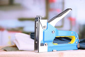 Construction stapler with fabric on cork board on bright background — Foto Stock