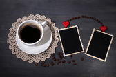 Samenstelling met koffiekopje, decoratieve harten en oude foto's in het lege, op houten achtergrond — Stockfoto