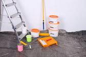 Buckets with paint and ladder on wall background. Conceptual photo of repairing works in  room  — Stok fotoğraf