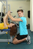Entrenador joven y mujer comprometida con las pesas en el gimnasio — Foto de Stock