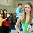 Stock Photo: Young womans engaged in simulator in gym