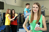 Young womans engaged in simulator in gym — Stockfoto