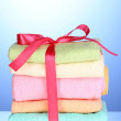 Stock Photo: Colorful towels with ribbon on blue background