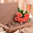 Stock Photo: Delicious chocolates in box with flowers on gold background