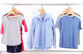 Different clothes on hangers, on gray background — Stock Photo