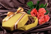 Delicious chocolates in box with flowers on brown background — Stock Photo