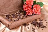Delicious chocolates in box with flowers on gold background — Stok fotoğraf