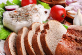 Slices of bread and lard with vegetables on table close up — Stock Photo