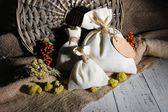 Textile sachet pouch with dried flowers, herbs and berries on wooden table, on sackcloth background — Stock Photo