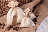 Sacs avec des grains de café sur la table en bois, sur fond d'un sac — Photo