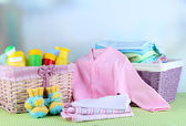 Pile of baby clothes  in basket, on table on color background — Stock Photo
