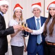 Successful young businesspeople at Santa hat at office — Stock Photo