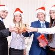 Successful young businesspeople at Santa hat at office — Stock Photo #42230135