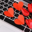 Stock Photo: Red hearts and flowers on computer keyboard close up