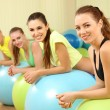 Group of young people training with gymnastic ball in gym — Stock Photo